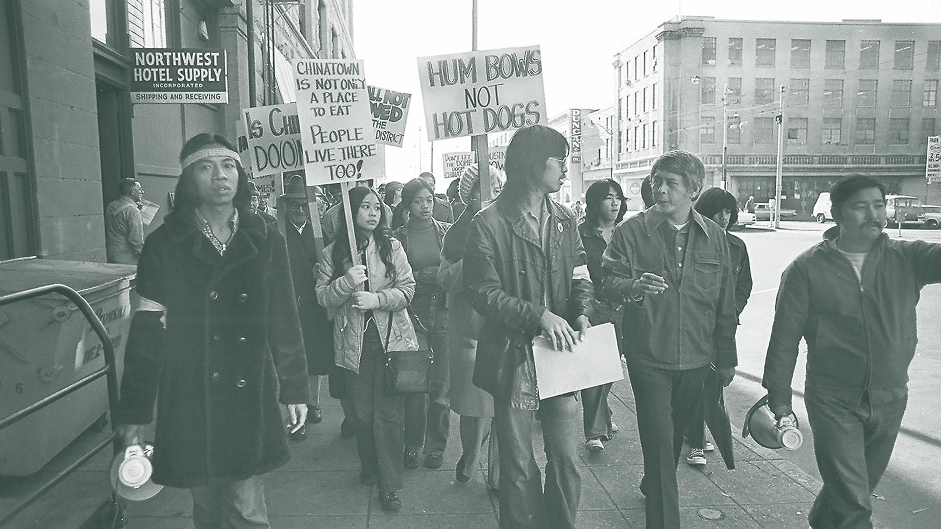 Crowd of Asian American Pacific Islanders marching with signs down a sidewalk in 1972. Signs say: Humbows not Hot Dogs, Chinatown is not only a place to eat. People live there too.